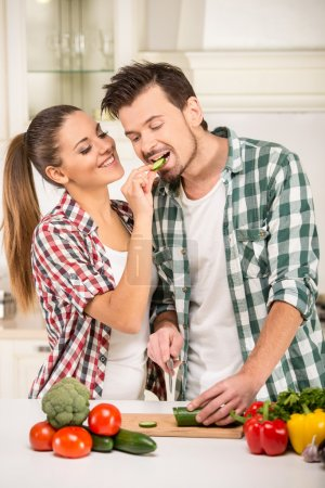 Photo for Beautiful young couple in the kitchen while cooking. - Royalty Free Image