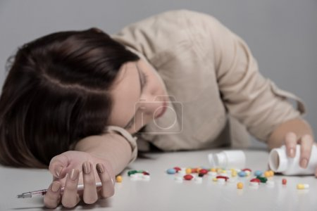 Photo for Pills lying on the table before suffering from the pain the young woman. - Royalty Free Image