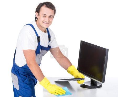 Photo pour Un jeune homme souriant nettoie le bureau. Fond blanc . - image libre de droit
