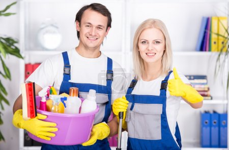 Photo for Young smiling couple are holding cleaning tools. - Royalty Free Image