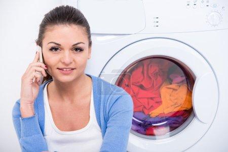 Photo pour La belle jeune femme est s'asseyant sur l'étage près de la machine à laver et parlant par le téléphone. - image libre de droit