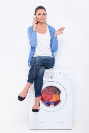 Photo pour La belle jeune femme s'assied sur la machine à laver et parle par téléphone. - image libre de droit