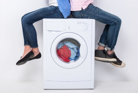 Photo for Young couple are sitting on the washing machine, on the white background. - Royalty Free Image