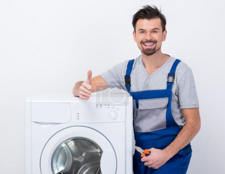Photo pour Smiling repairman is repairing a washing machine on the white background. - image libre de droit