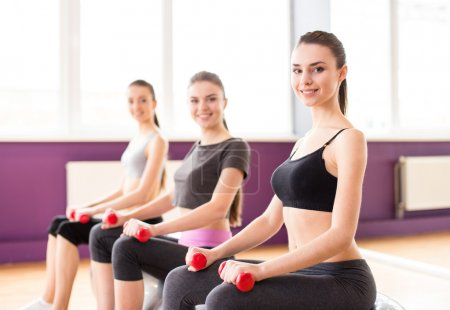 Photo for Fitness, sport, training and lifestyle concept - three smiling woman with exercise balls and dumbbells in gym. - Royalty Free Image