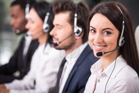 Photo pour Vue latérale de la ligne d'appel employés du centre sont souriant et travailler sur les ordinateurs. - image libre de droit