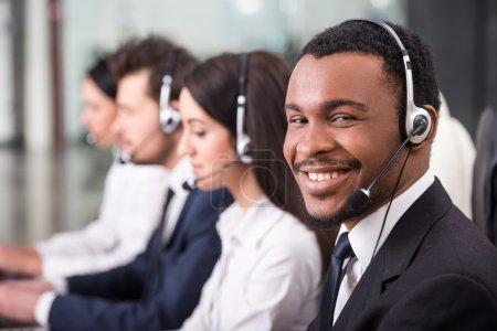 Photo pour Vue latérale de la ligne d'appel employés du centre sont souriant et travailler sur les ordinateurs. L'un d'eux fatigués et dorment. - image libre de droit