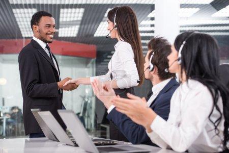 Photo pour Vue latérale de la ligne d'appel employés du centre sont souriant et travailler sur les ordinateurs. Deux d'entre eux sont serrer la main. - image libre de droit