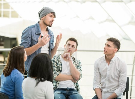 Foto de Young man is sharing his problems with people. View of man is telling something and gesturing while group of people are sitting in front of him and listening. - Imagen libre de derechos