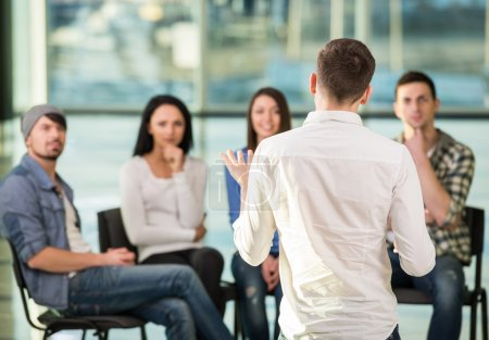 Photo for Young man is sharing his problems with people. View of man is telling something and gesturing while group of people are sitting in front of him and listening. - Royalty Free Image