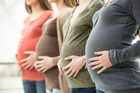 Side view of three pregnant women are touching the...