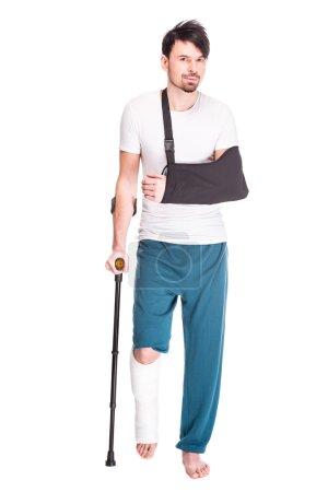 Photo pour Vue pleine longueur d'un jeune homme avec la jambe et la main cassées utilise la béquille isolée sur fond blanc . - image libre de droit