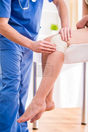 Doctor is rewinding knee bandage to young woman....