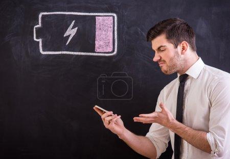 Photo pour Jeune homme en colère tient son smartphone avec batterie faible . - image libre de droit