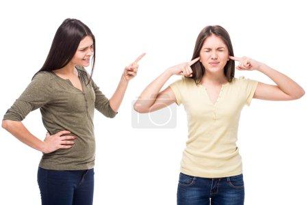 Photo pour Problèmes entre générations concept. Adolescent fermé ses oreilles avec ses mains tandis que sa mère lui crie dessus . - image libre de droit