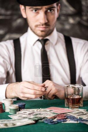 Photo pour Joueur de poker confiant. Un jeune homme sérieux en chemise, chapeau et bretelles est assis à la table de poker avec des cartes, des jetons et un verre de whisky . - image libre de droit