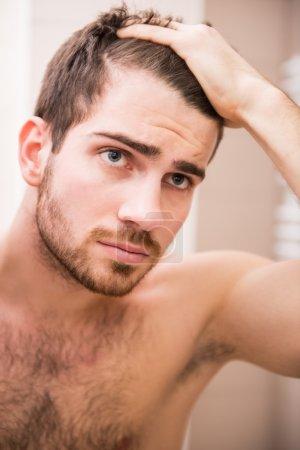 Photo pour L'homme beau vérifie la ligne des cheveux tout en regardant le miroir. - image libre de droit