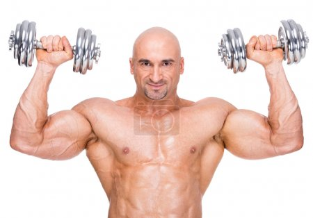 Photo for Muscular bodybuilder exercising with two weights on white background. - Royalty Free Image
