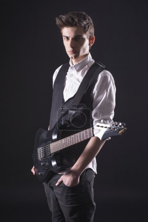 Photo for Young guitarist with the electric guitar, isolated on dark background is looking at the camera. - Royalty Free Image