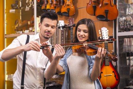Photo pour Jeune homme enseigne fille à jouer du violon au magasin de musique . - image libre de droit