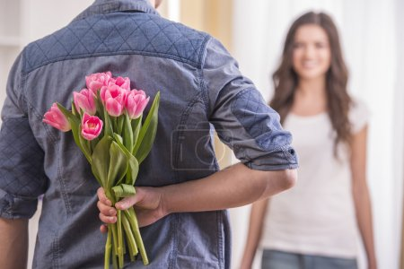 Photo for The young man is hiding flowers behind their backs to his girlfriend at home. - Royalty Free Image
