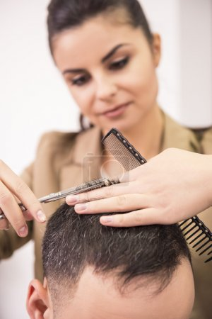 Female hairdresser is cutting hair of man client....
