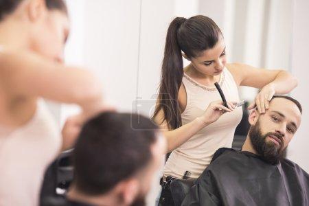 Photo pour Coiffeur rasage d'un rasoir à l'ancienne et peignes de client satisfait dans le salon de coiffure professionnel . - image libre de droit