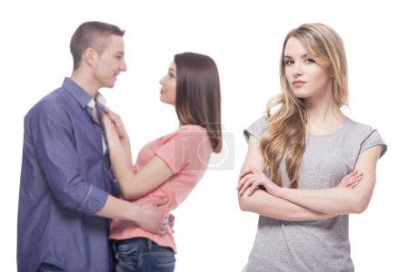 Photo pour Triangle amoureux. Solitude. Jeunes femmes tristes debout avec les bras croisés alors que des femmes et des hommes étreignant un autre. isolé sur fond blanc. - image libre de droit