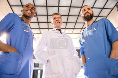 Photo for Three handsome male doctors standing in hospital. - Royalty Free Image