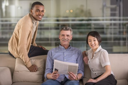 Photo for Two handsome men and yong woman seating on sofa with newspaper. And looking at camera. - Royalty Free Image