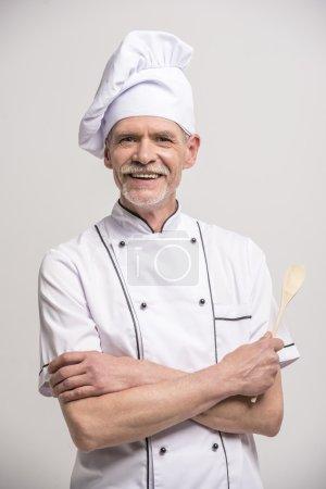 Photo pour Chef cuisinier masculin senior en uniforme avec les mains croisées avec une fouille en bois sur fond gris . - image libre de droit