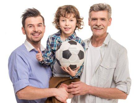 Foto de Retrato de generación. Abuelo, padre e hijo, aisló un fondo blanco. Niño sosteniendo en las manos bola. - Imagen libre de derechos