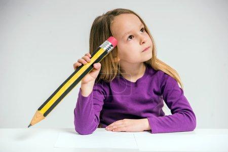 Photo pour Mignon dessin de petite fille avec grand crayon à la table sur fond gris . - image libre de droit