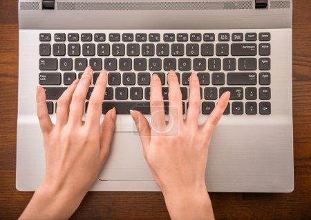 Photo pour Vue du dessus des mains tapant sur le clavier de l'ordinateur portable dans le bureau . - image libre de droit