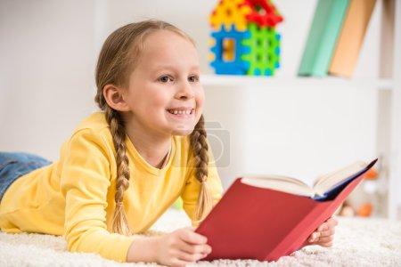 Photo pour Petite jolie fille en pull jaune livre de lecture sur fond coloré . - image libre de droit