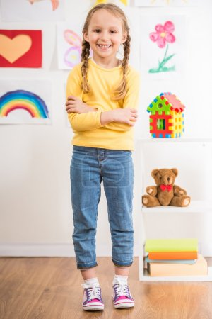 Photo for Little pretty smiling girl in full length in yellow  pullover on colorful background. - Royalty Free Image