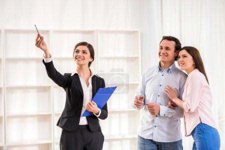 Photo pour L'agent immobilier féminin montre un plat au jeune couple. - image libre de droit