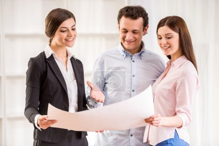 Young couple with realtor are watching the plan of...