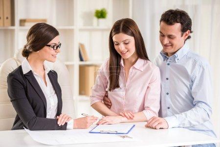 Photo pour Jeune agent immobilier expliquer le contrat de location pour jeune couple. - image libre de droit