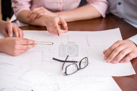 Photo pour Jeune agent immobilier montrant le contrat avec agencement dans un appartement pour un jeune couple. - image libre de droit