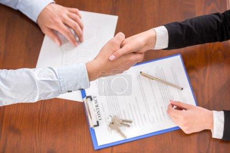 Photo pour Vue de dessus de la poignée de main d'un agent immobilier et d'un client . - image libre de droit