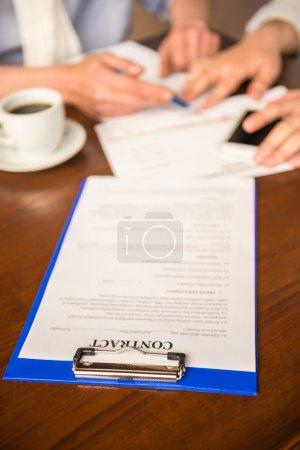 Photo pour Plan rapproché des hommes d'affaires s'asseyant à la table en bois avec le café et signant le contrat. - image libre de droit