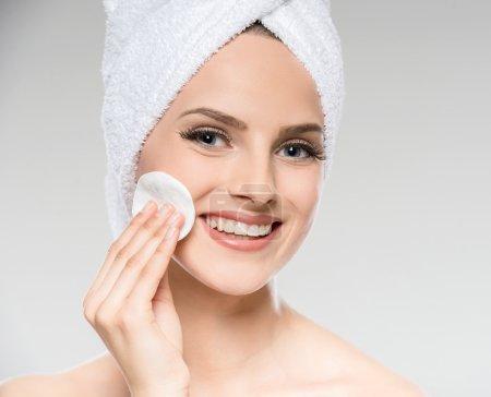Photo pour Portrait de belle jeune femme avec peau nettoyante serviette avec coton-tige . - image libre de droit