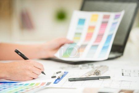 Photo pour Gros plan de designer d'intérieur travaillant avec des échantillons de couleur dans son bureau . - image libre de droit