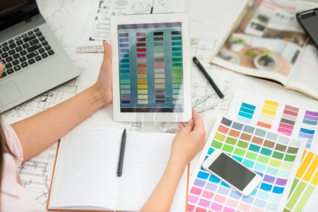 Photo pour Gros plan du concepteur tenant la tablette numérique dans les mains et travaillant avec des échantillons de couleur . - image libre de droit