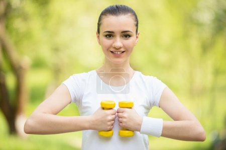 Photo for Young athletic girl making exercises with dumbbells outdoors. - Royalty Free Image