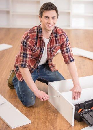Photo pour Jeune homme habillé de meubles montage occasionnels dans Maison Neuve. - image libre de droit