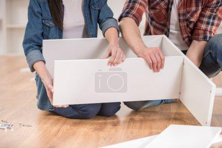 Photo pour Gros plan de jeune couple mettre ensemble mobilier d'auto-assemblage lorsqu'elles se déplacent dans leur nouvelle maison. - image libre de droit