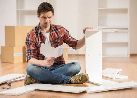 Photo pour Concentré de jeune homme, lire les instructions pour assembler les meubles dans la cuisine à la maison. - image libre de droit