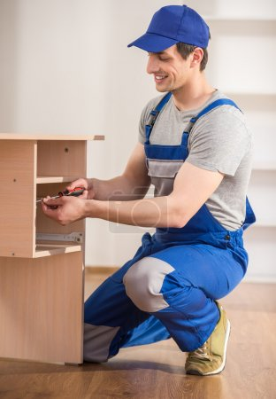 Photo pour Jeune réparateur montage nouvelle table à l'intérieur de la maison. - image libre de droit